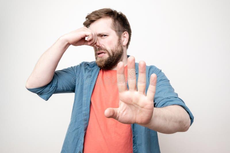 Homem caucasiano, barbudo, aperta o nariz com a mão por causa de um odor desagradável e coloca a palma para a frente, bloqueando  fotografia de stock royalty free
