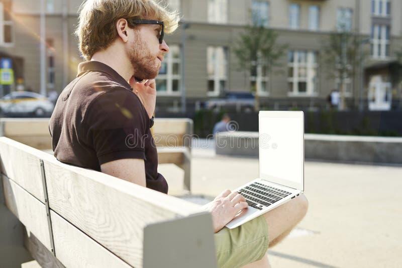 Homem caucasiano considerável do moderno que trabalha no assento do portátil exterior em um parque Dia da luz do sol do verão Con foto de stock