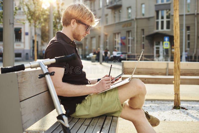Homem caucasiano considerável que usa o assento do portátil exterior em um parque Dia da luz do sol do verão Conceito de executiv imagem de stock