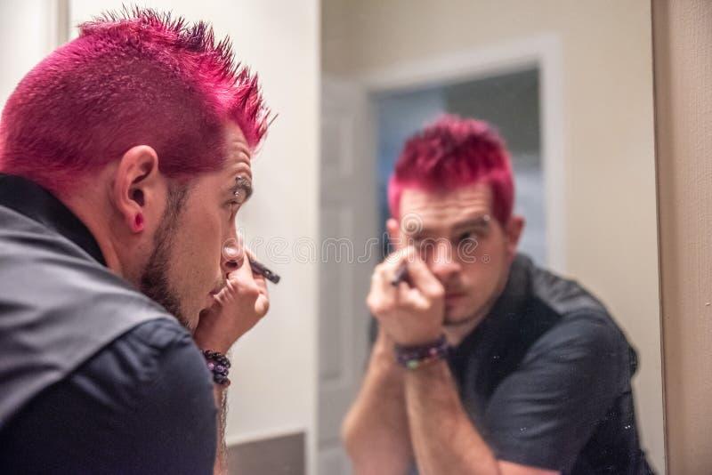Homem caucasiano diverso com o cabelo cor-de-rosa cravado que aplica o lápis de olho no espelho fotografia de stock royalty free