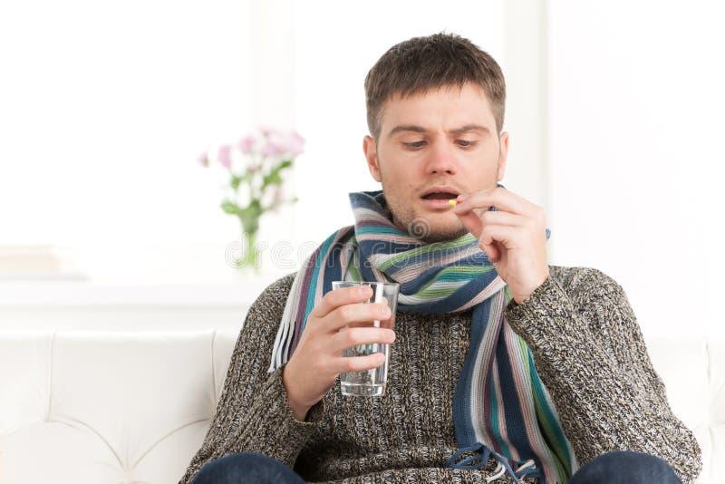 Homem caucasiano doente que guarda comprimidos e água imagem de stock