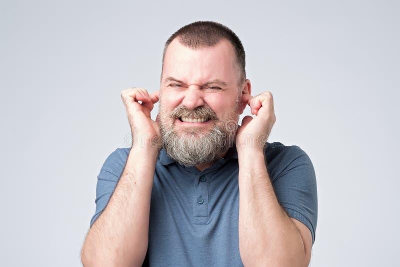 Homem caucasiano irritado para evitar para ouvir a incomodidade do ruído alto fotos de stock royalty free