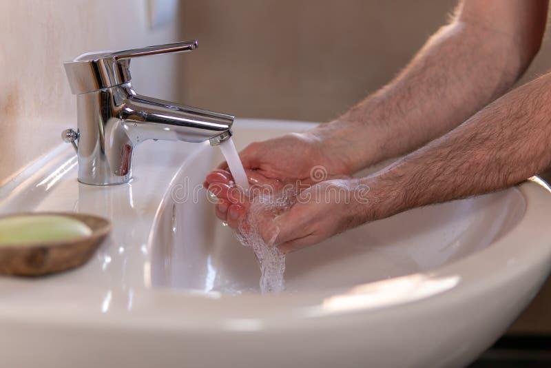 Homem caucasiano lavando cuidadosamente as mãos na bacia de lavagem sob torneira d'água Higiene pessoal como coronavírus Alastram imagem de stock royalty free