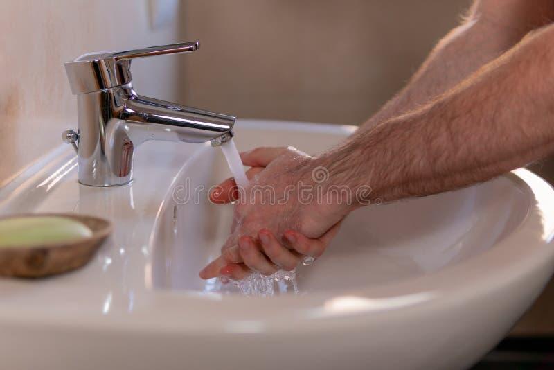 Homem caucasiano lavando cuidadosamente as mãos na bacia de lavagem sob torneira d'água Higiene pessoal como coronavírus Alastram imagens de stock royalty free