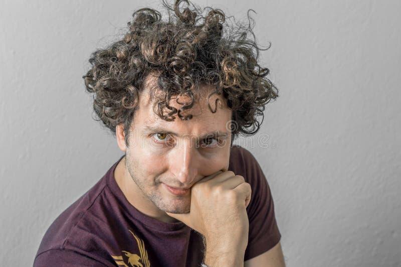 Homem caucasiano novo com o cabelo encaracolado que olha à câmera no fundo branco foto de stock