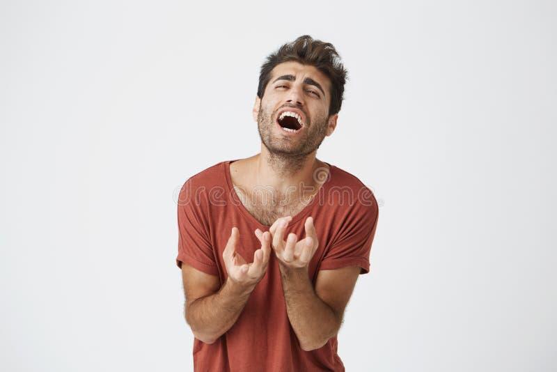 Homem caucasiano novo infeliz expressivo no penteado à moda do tshirt vermelho e barba que joga o momento extremamente trágico de fotos de stock