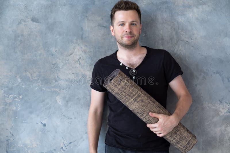 Homem caucasiano novo no t-shirt preto que guarda a posição da esteira da ioga perto da parede do estúdio imagem de stock royalty free