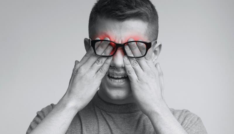 Homem caucasiano novo nos vidros que friccionam seus olhos foto de stock royalty free