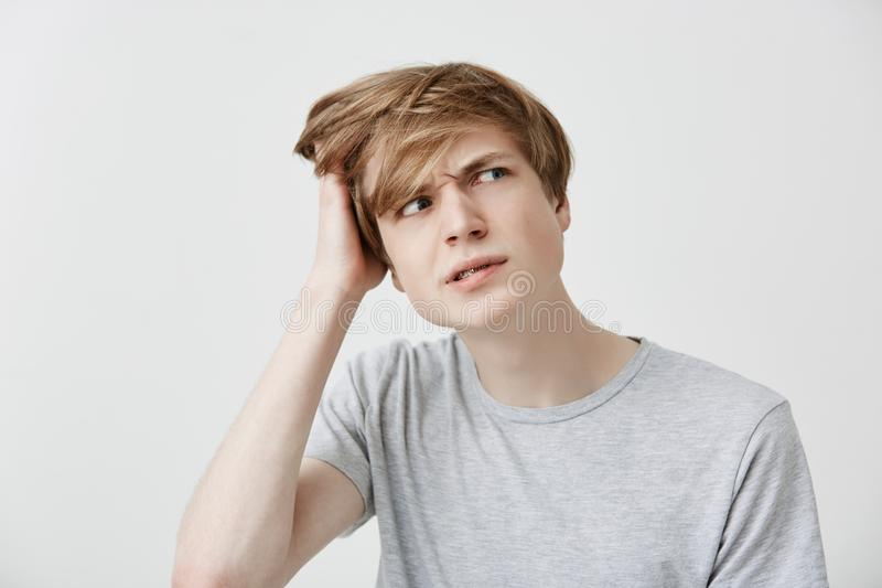 Homem caucasiano novo perplexo à nora no t-shirt cinzento que olha de lado com a expressão confusa e confundida, riscando foto de stock royalty free