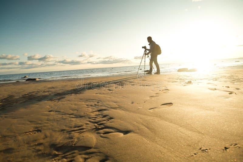 Homem caucasiano novo que faz a foto da paisagem no beira-mar imagens de stock