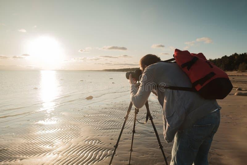 Homem caucasiano novo que faz a foto da paisagem no beira-mar imagem de stock royalty free