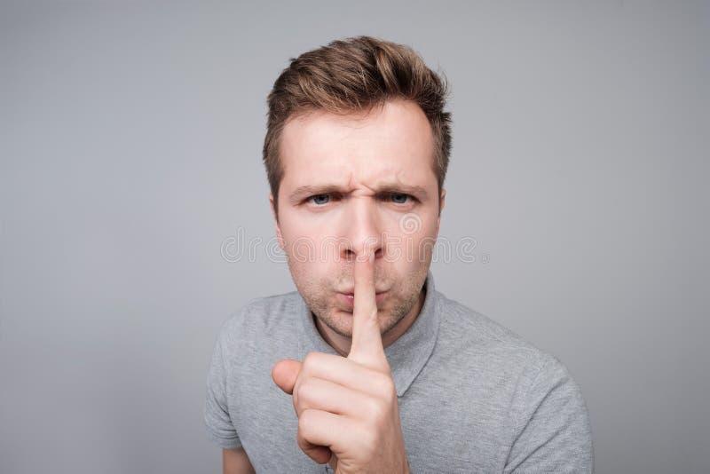 Homem caucasiano novo que faz o gesto do silêncio fotos de stock