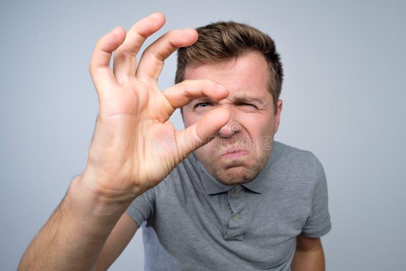 Homem caucasiano novo que gesticula com a mão que mostra o sinal pequeno do tamanho com dedos foto de stock royalty free