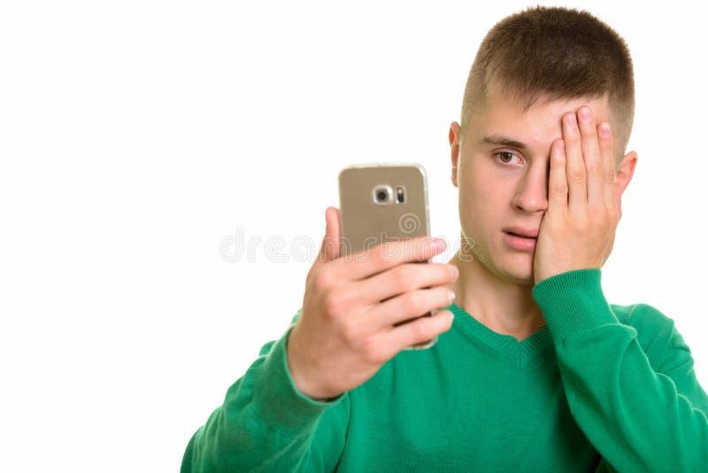 Homem caucasiano novo que guarda o telefone celular que olha forçado imagem de stock royalty free