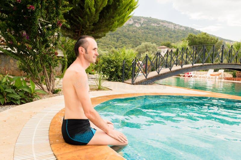 Homem caucasiano novo que relaxa perto da piscina em um recurso imagem de stock
