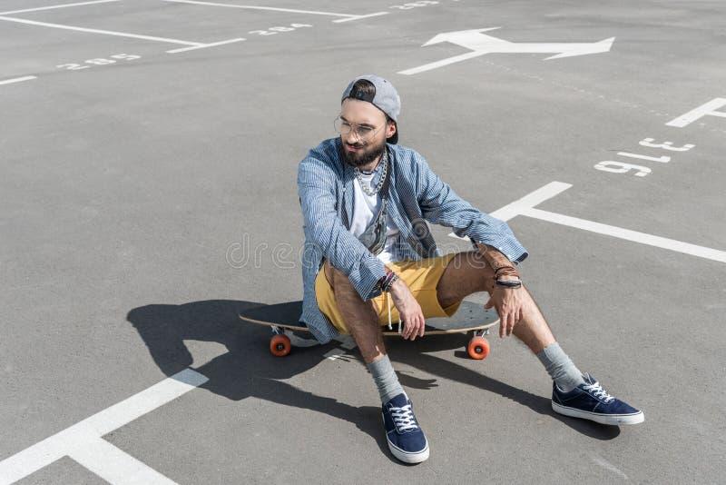 Homem caucasiano novo que senta-se no longboard na rua fotos de stock