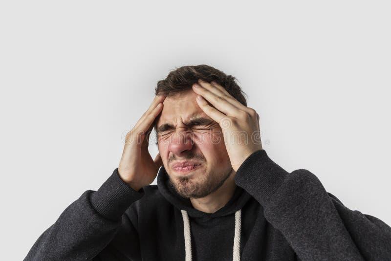 Homem caucasiano novo que sofre da enxaqueca terrível Isolado no fundo branco Conceito das dores de cabeça fotos de stock royalty free