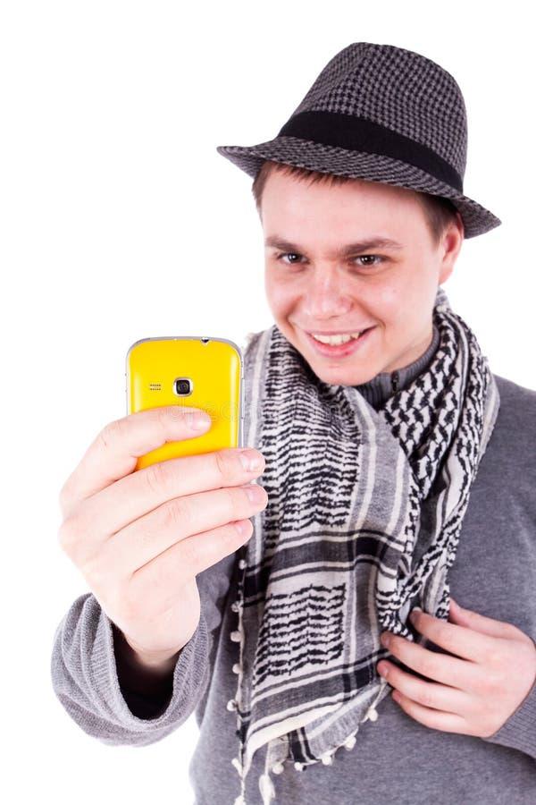 Homem caucasiano novo que toma a foto com um telefone amarelo foto de stock royalty free
