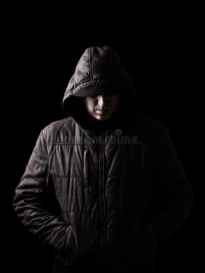Homem caucasiano ou branco assustador e assustador que esconde nas sombras imagens de stock
