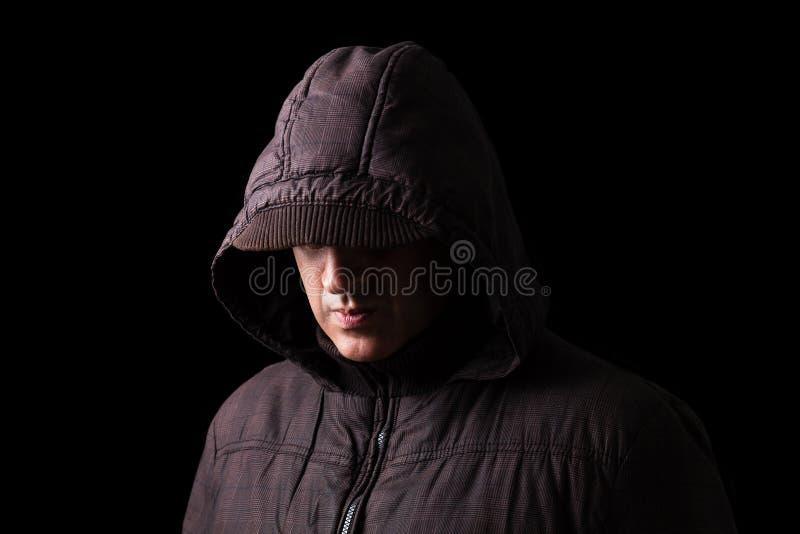 Homem caucasiano ou branco assustador e assustador que esconde nas sombras, com a cara e a identidade escondidas com a capa foto de stock