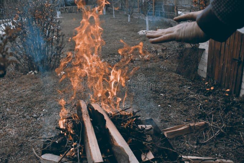 Homem caucasiano que aquece suas mãos na fogueira em uma atmosfera escura fria foto de stock royalty free