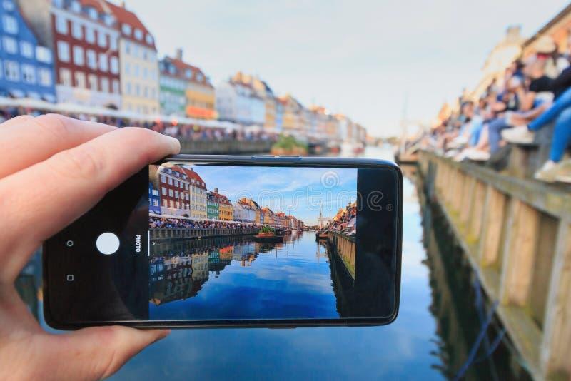Homem caucasiano que captura a foto de Nyhavn em Copenhaga durante a celebração do fest de Sankthans fotos de stock