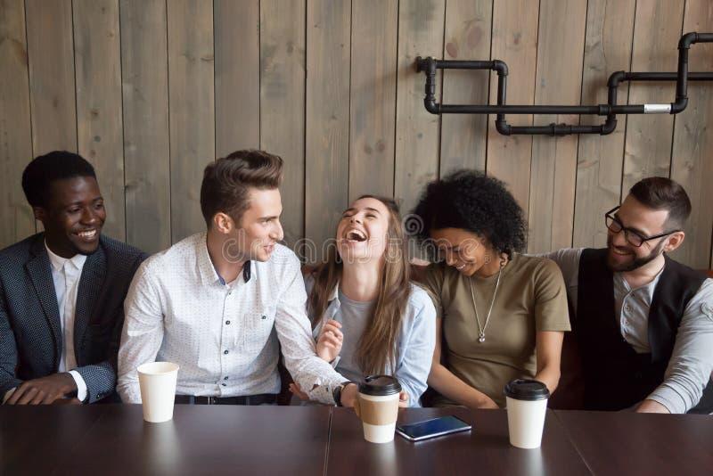 Homem caucasiano que graceja na reunião do café que faz amigos multirraciais imagens de stock royalty free