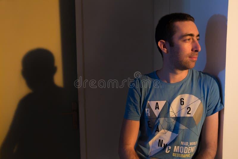Homem caucasiano que inclina-se contra a parede e que olha afastado foto de stock