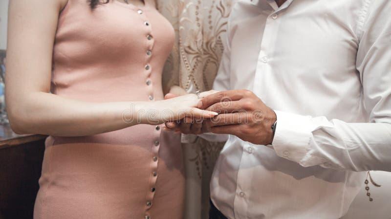 Homem caucasiano que põe sobre o anel de noivado do dedo da menina imagens de stock royalty free