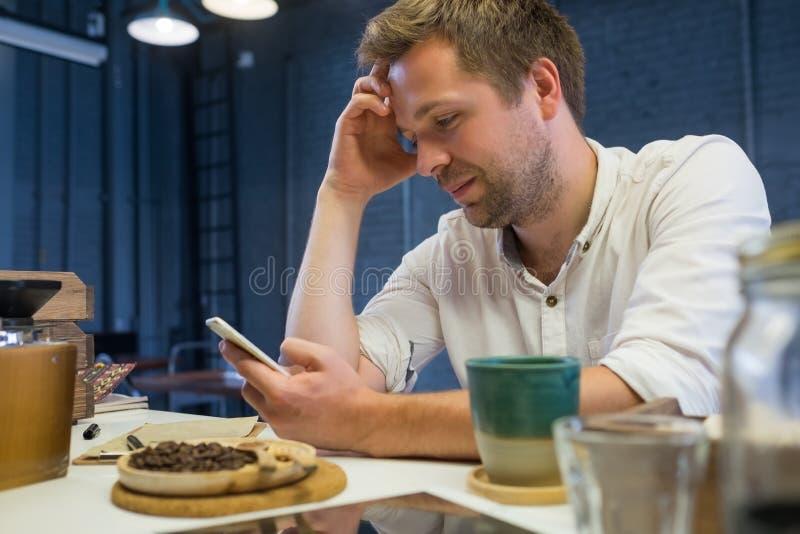 Homem caucasiano que senta-se apenas no café e que espera seus amigos imagens de stock