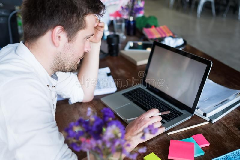 Homem caucasiano que trabalha no portátil ao sentar-se em seu lugar moderno do escritório Conceito dos jovens que usam o lugar co imagens de stock