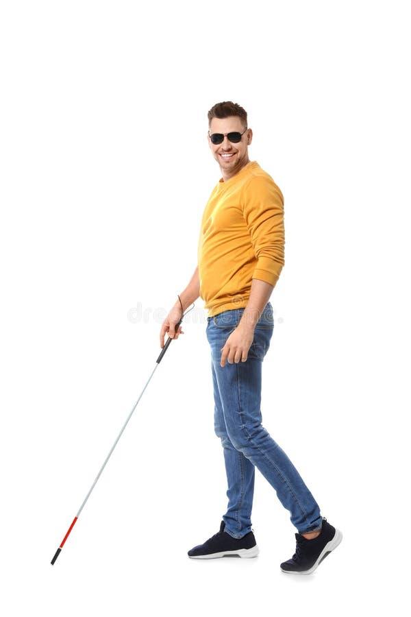Homem cego em vidros escuros com o bastão de passeio no branco imagens de stock royalty free