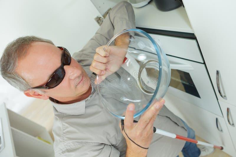 Homem cego na cozinha em casa imagens de stock royalty free