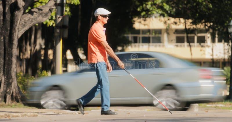 Homem cego que cruza a estrada com carros e tráfego fotografia de stock