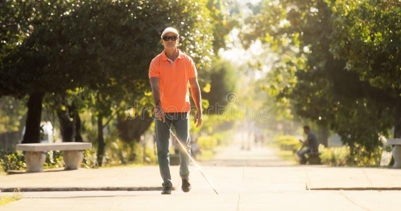 Homem cego que cruza a rua e que anda com bastão fotografia de stock royalty free