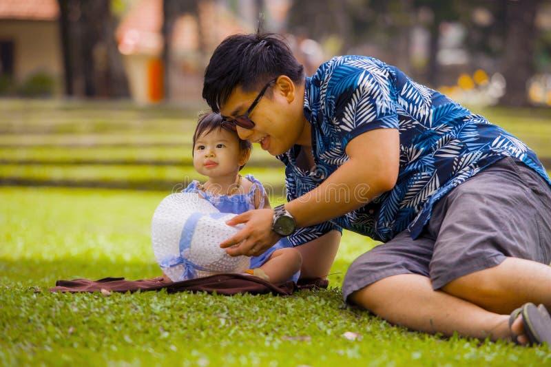 Homem chinês asiático brincalhão feliz como o pai de amor que aprecia a filha doce e bonita do bebê que senta junto o jogo na gra fotografia de stock