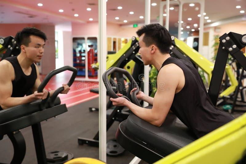 Homem chinês asiático na força do treinamento do homem do esporte de ŒFitness do ¼ do ï do gym no gym imagem de stock royalty free