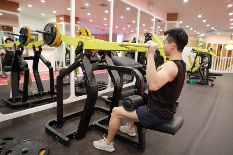 Homem chinês asiático na força do treinamento do homem do esporte de ŒFitness do ¼ do ï do gym no gym foto de stock royalty free