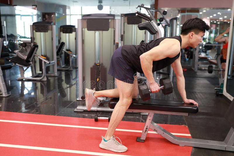 Homem chinês asiático no homem novo de ŒFitness do ¼ do ï do gym no gym que faz exercícios com pesos fotos de stock