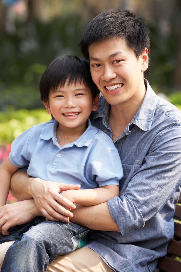 Homem chinês com o filho que relaxa no banco de parque foto de stock