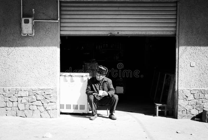 Homem chinês idoso que bebe um copo do chá na rua foto de stock royalty free