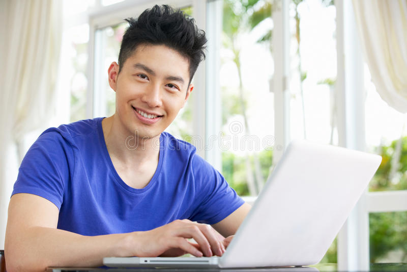 Homem chinês novo preocupado que usa o portátil em casa
