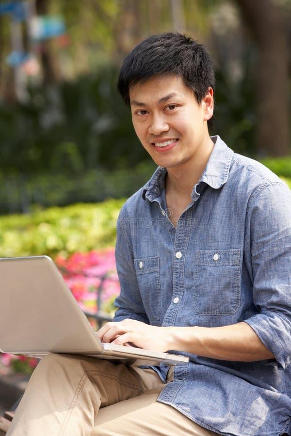 Homem chinês novo que usa o portátil enquanto relaxando fotos de stock royalty free