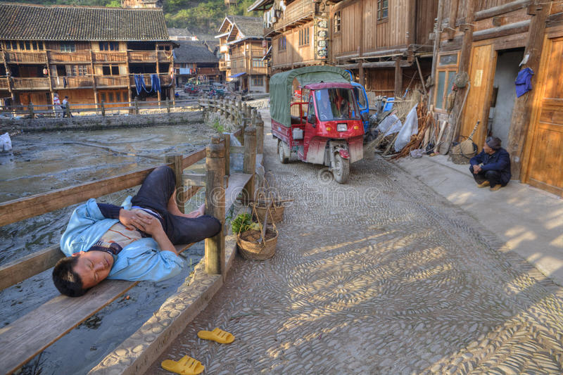 Homem chinês que encontra-se no meio do banco da rua da vila, China fotografia de stock royalty free