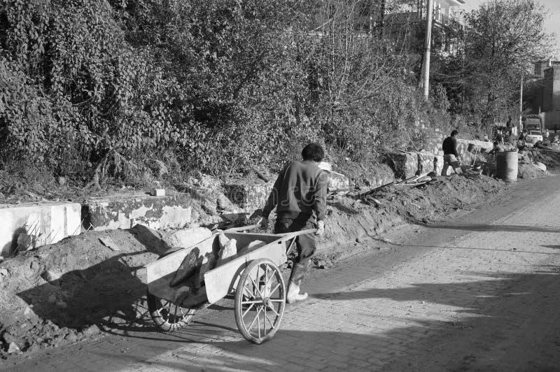 Homem chinês que trabalha na rua com um carrinho de mão foto de stock