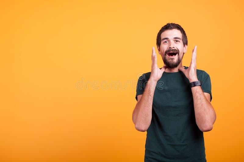 Homem chocado com mãos em sua cara que olha a câmera fotografia de stock royalty free