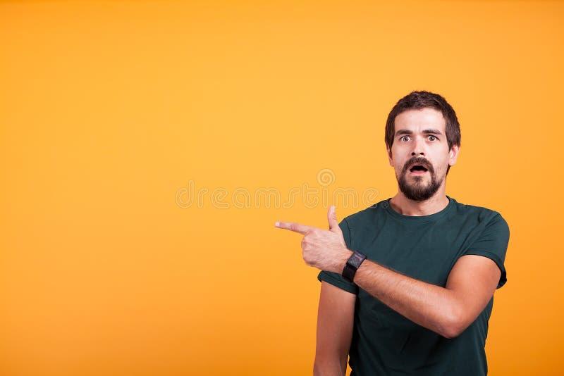 Homem chocado expressivo que aponta em seu direito com sua boca aberta fotografia de stock