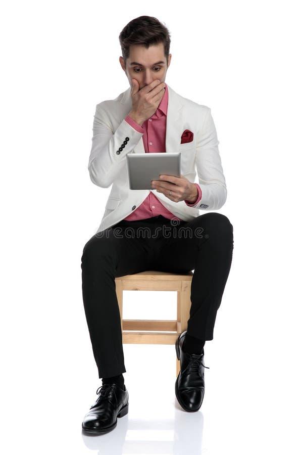 Homem chocado que cobre sua boca ao ler a notícia na tabuleta fotos de stock royalty free