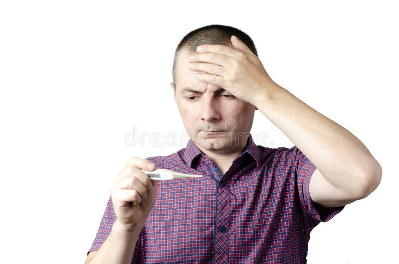 Homem chocado que l? sua temperatura no term?metro Foto do v?rus de sofrimento da gripe do frio e do inverno do homem doente fotografia de stock