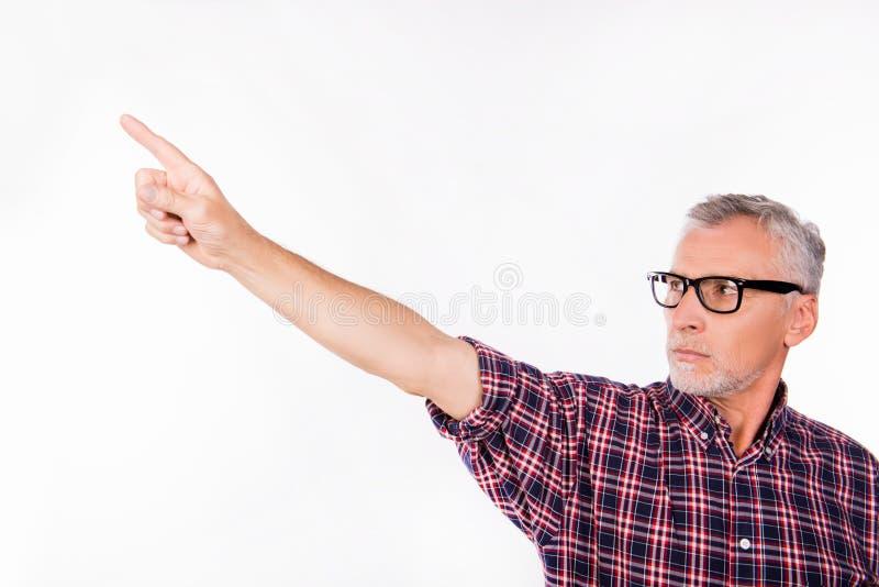Homem cinza confiável de idade com óculos apontando para longe imagens de stock royalty free